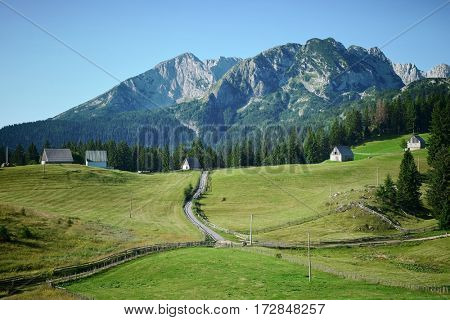 road crosses small village under the mountains of Durmitor National Park, Montenegro