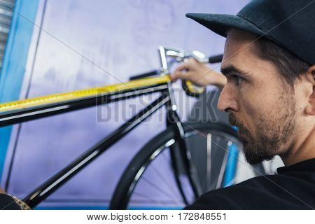 Close-up of bearded craftsman taking measurements of bicycle