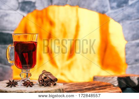 Mulled wine in irish glass with spices on serving boards over hearth background