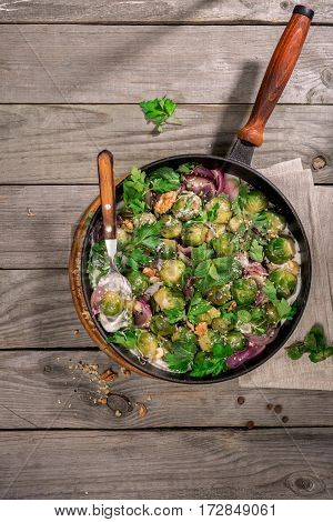 Roasted sprouts in the greek yogurt in a cast iron frying pan on a wooden table top view