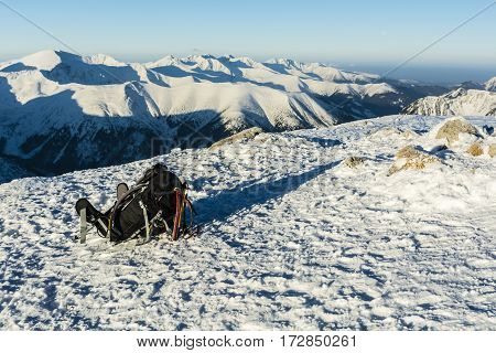 Backpack, Ice Axes And Trekking Poles On A Background Of Mountains