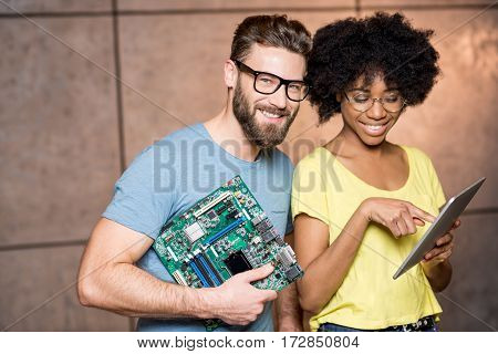 Multi ethnic programmers dressed casually standing together with computer motherboard and digital tablet on the wall background indoors