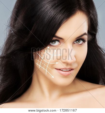 Close-up portrait of beautiful, fresh, healthy and sensual girl with arrows on her face. Medicine, spa and skin care concept.