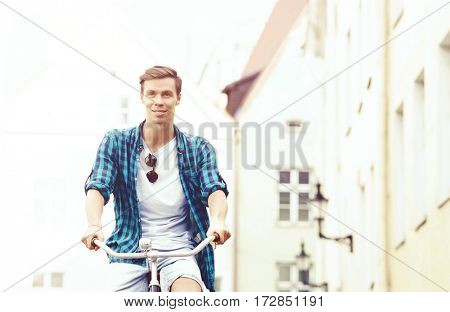 Attractive and handsome hipster riding a bicycle around town. Traveling, vacation concept.