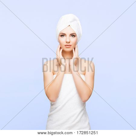 Young, beautiful and natural woman wrapped in towel over blue background.