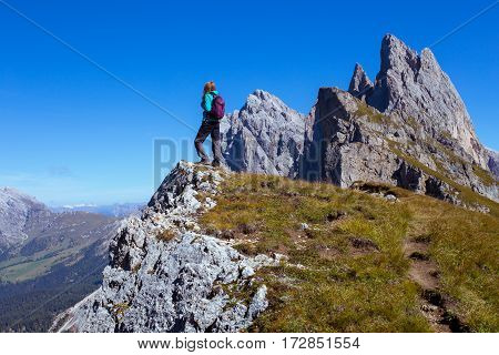 girl hiker standing on a cliff at the mountains Dolomites and views of the valley Italy. Seceda