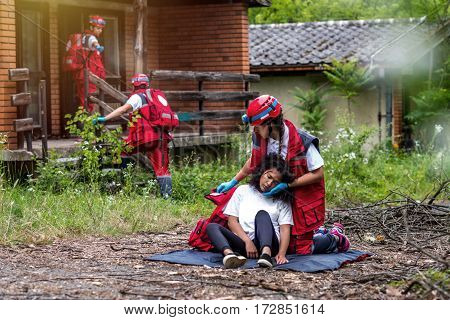 Rescue team helping injured female victim, color image