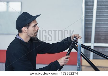 Bearded man working with metal bars at workshop