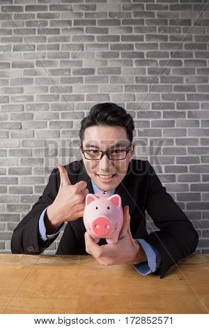 business man take piggy bank in the office asian