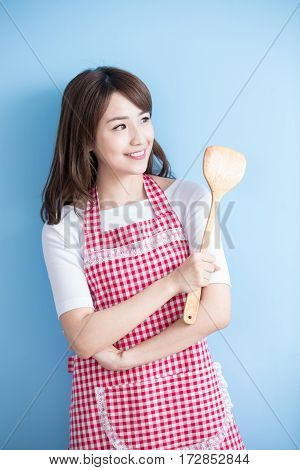 beauty housewife take rice spoon and look somewhere isolated on blue background