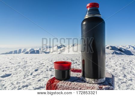 Vacuum Flask Of Hot Tea On A Table With A Boundary Marker In The Winter In The Mountains.