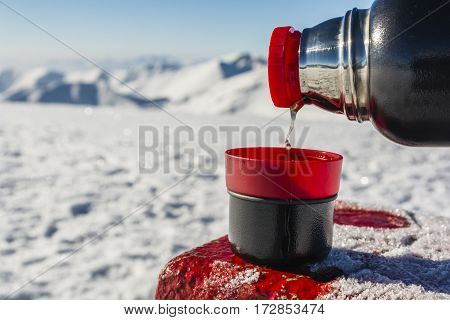 Pouring hot tea from a thermos into a cup in the winter in the mountains.