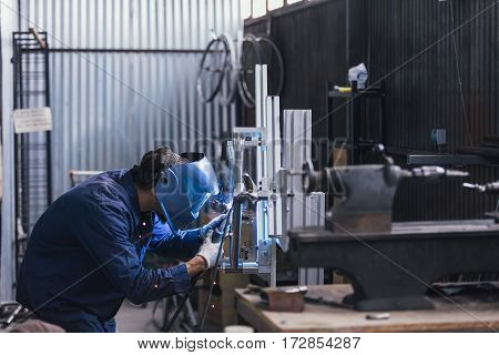 Unrecognizable man in mask working with welding machine