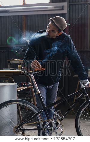 Bearded craftsman smoking while holding his new bicycle in workshop