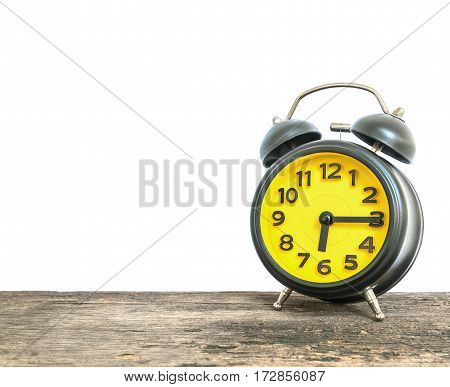 Closeup black and yellow alarm clock for decorate show a quarter past six or 6:15 a.m. on old brown wood desk isolated on white background with copy space