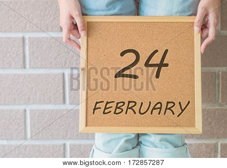 Closeup calendar at the cork board in hand of asian woman in front of her legs with 24 february word on brick wall textured background