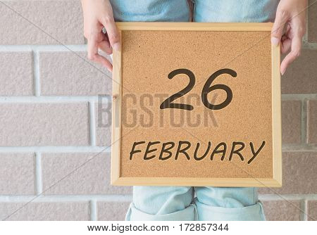 Closeup calendar at the cork board in hand of asian woman in front of her legs with 26 february word on brick wall textured background