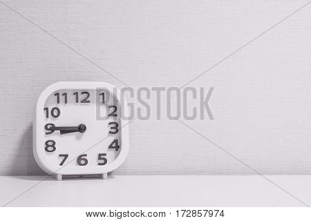 Closeup white clock for decorate show a quarter to nine p.m. or 8:45 a.m. on white wood desk and cream wallpaper textured background in black and white tone with copy space