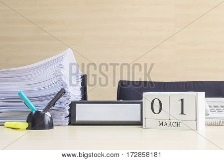 Closeup white wooden calendar with black 1 february word on blurred brown wood desk and wood wall textured background in office room view with copy space selective focus at the calendar