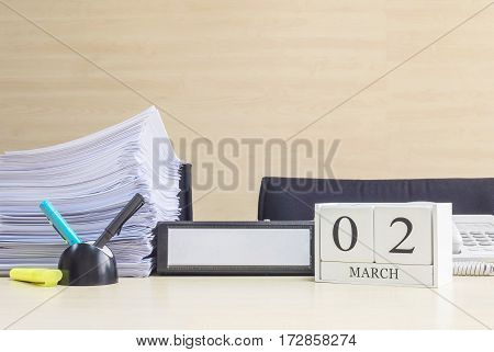 Closeup white wooden calendar with black 2 february word on blurred brown wood desk and wood wall textured background in office room view with copy space selective focus at the calendar