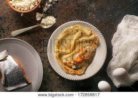 Russian-style pancakes with lox and cottage cheese on the plate