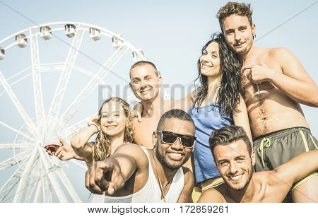 Group of multiracial happy friends taking selfie and having fun at luna park ferris wheel - Summer joy travel concept on multi ethnic friendship - Retro vintage filter with focus on afro american guy