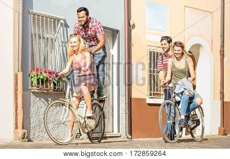 Happy multiracial friends couple having fun riding bicycle in city old town - Friendship concept with multicultural young people on funny attitude biking together - Warm afternoon color tone filter