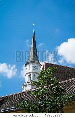 VIENNA, AUSTRIA - JULY 29, 2016: A church tower at the old center of Vienna above the tile roofs and a tree on a sunny summer day.