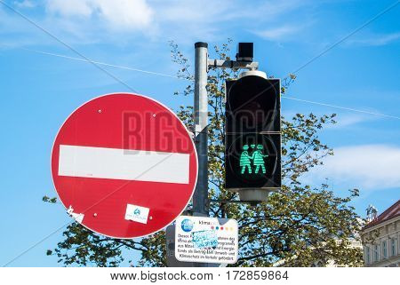 VIENNA AUSTRIA - JULY 29 2016: A close-up view of a green traffic light with an image of two walking lesbian girls at the center of Vienna Austria.