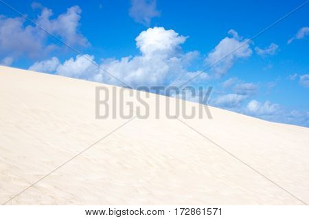 Slope hill sand on yellow dunes on blue sky background. Sustainable ecosystem. Canary island, Fuerteventura dune
