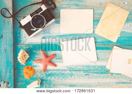 Top view composition - Blank paper photo frames with starfish shells coral and items on wooden table. Concept of remembrance and nostalgia in summer tourism travel and vacation. vintage color tone.