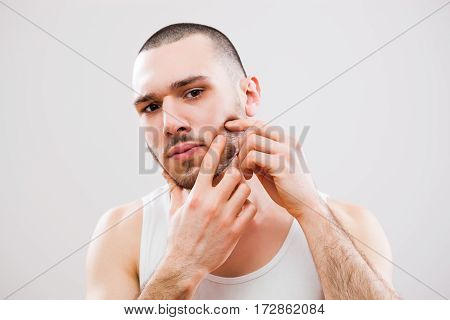 Young man is squeezing pimple on his cheek.