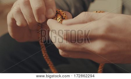 Man's hands tying a mountaineering knot on a rope. Close up.