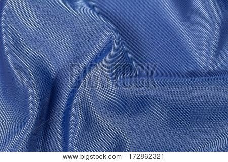 Silk background texture of blue shiny fabric close up