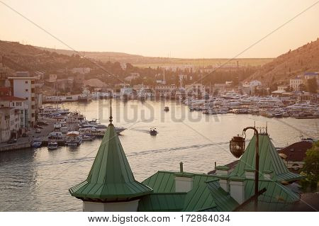 Sailing boats and yachts anchored in calm bay at sunset. Summer vacation and tourism concept