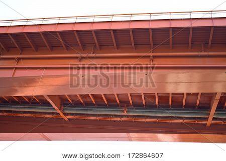 Under red steel bridge construction over white