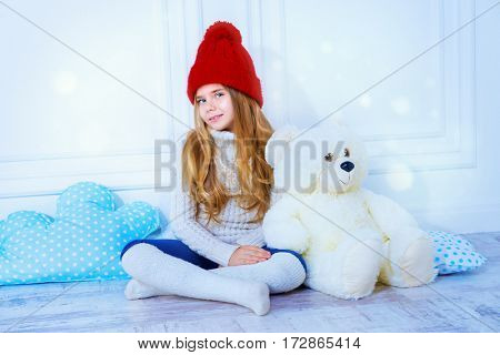Cute little 7 year old girl wearing knitted winter clothes posing with her teddy bear. Children's fashion.