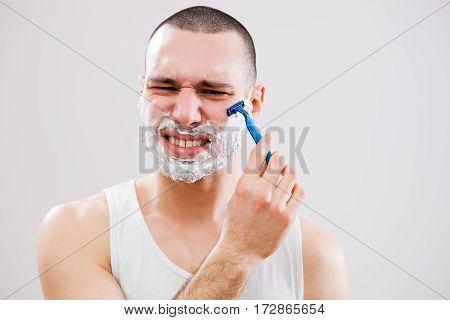 Young man cut himself while shaving his beard.