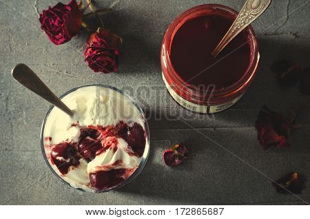 Sundae Ice cream with cherry in chocolate topping, and dried rose flowers on dark background. Love, Valentine's day concept. Horizontal, top view, toned