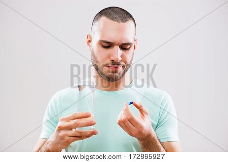 Portrait of young man who is taking a pill because of illness.