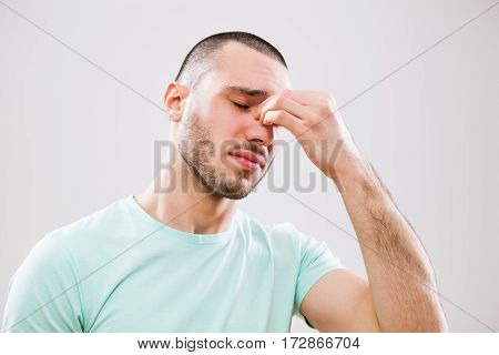Portrait of young man who is having pain in his sinus.