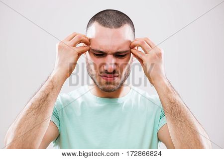 Portrait of young man who is having headache.