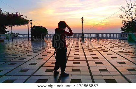 Silhouette of a short curly hair asian woman standing to take the photo of dramatic sunrise landscape with camera at view point balcony of Wat Pra That Doi Suthep Chianf Mai Thailand