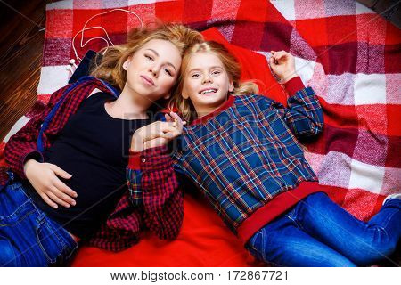 Family concept. Two cute girls, older and younger sister sitting together on a floor. Children's fashion.