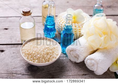 Spa setting in blue yellow and white colors. Bottles wih essential aroma oil towels candles and wispes on aged wooden background. Selective focus.