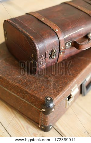 Brown vintage suitcases on the old wooden floor