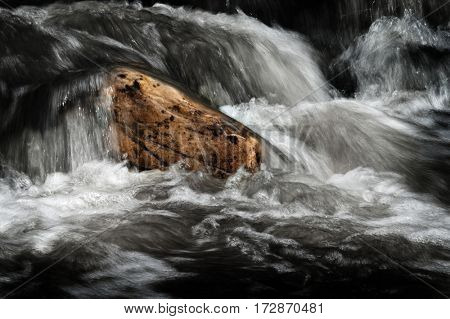 Water in a stream or creek flowing over rocks smooth motion