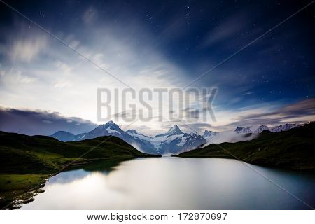 High mountain peaks glowing in the moonlight. Dramatic scene. Location place Bachalpsee in Swiss alps, Grindelwald valley, Bernese Oberland, Europe. Artistic picture. Discover the world of beauty.
