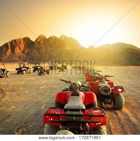 Quad bikes in desert at the sunset