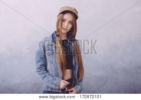 Closeup fashion studio portrait of hipster young tender woman in brown cap and denim vest over light grey background. Caucasian teen woman model posing indoors